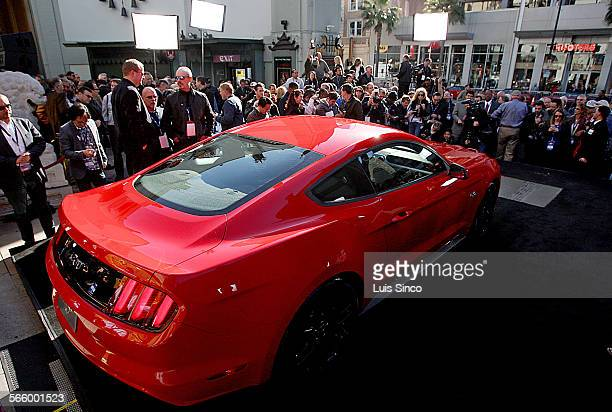 Car enthusiasts and members of the motor industry press watch the unveiling of the 2015 Ford Mustang at the TCL Chinese Theater in Hollywood on...