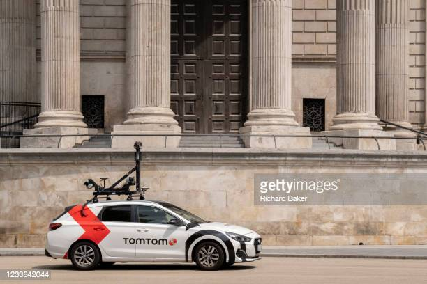 Car equipped with camera and mapping technology for the SatNav brand TomTom drives beneath the pillars and column architecture of Sir Christopher...