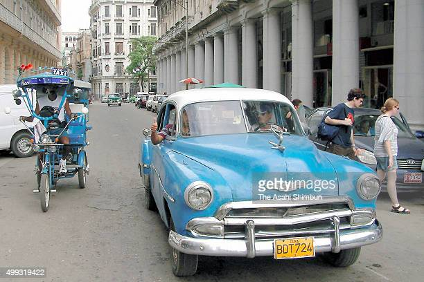 A US car exported before the Cuban revolution and a rickshaw are seen on the street on October 14 2007 in Havana Cuba
