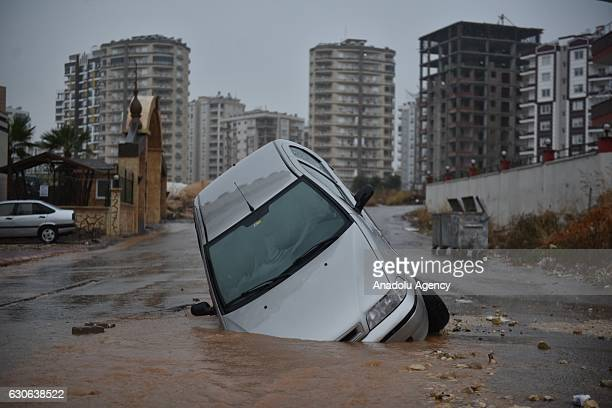 A car falls into a hole in a flooded street as heavy rainfall hits Mersin Turkey on December 29 2016