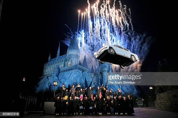 A car floats as participants swing sticks called magical wands during the opening ceremony of the new interactive attraction 'Wand Magic' as...