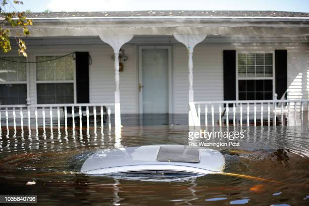 September 18: A car floats in front of a flooded home in the floodwaters of the Lumber River in Lumberton, N.C., Tuesday, September 18, 2018....