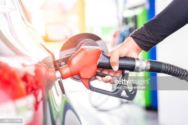 car fuels concept, oil station hand and fuel nozzle in car - gas tank stock photos and pictures