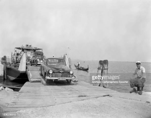 A car getting off a tug boat to the Autorimessa Piazzale Roma Venice circa 1950