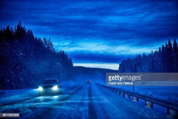 Car headlights on snow covered highway at dusk, Hemavan, Sweden