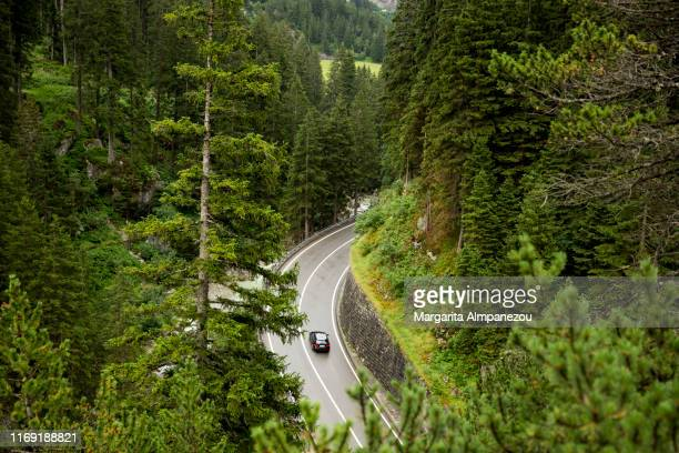 car in curved road passing through the mountains - ball passen stock-fotos und bilder