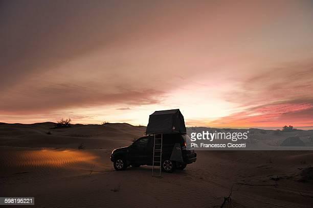Car in Sahara Desert at sunrise