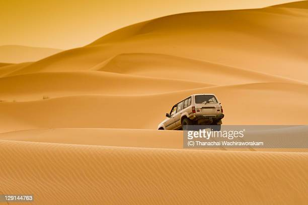 car in sand dunes - merzouga stock pictures, royalty-free photos & images