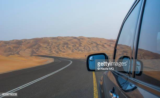 car in the desert road liwa, abudhabi, united arab emirates - gulf countries stock pictures, royalty-free photos & images