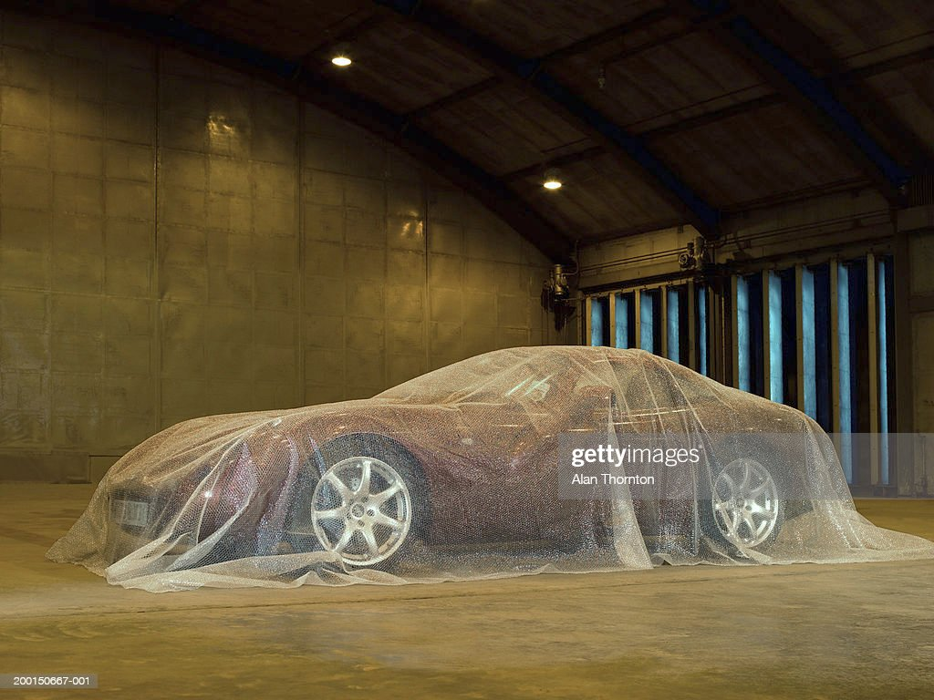 Car in warehouse, covered in bubble wrap : Stock Photo