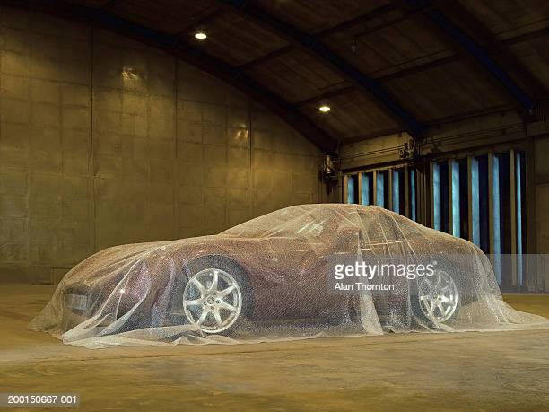 Car in warehouse, covered in bubble wrap
