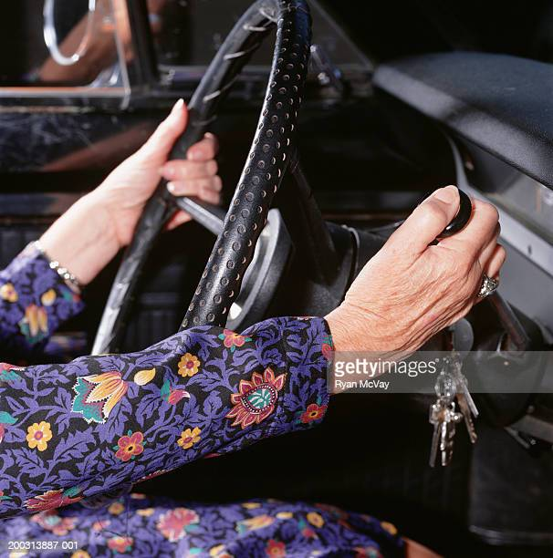 Car interior, close-up of senior woman changing gears, mid section