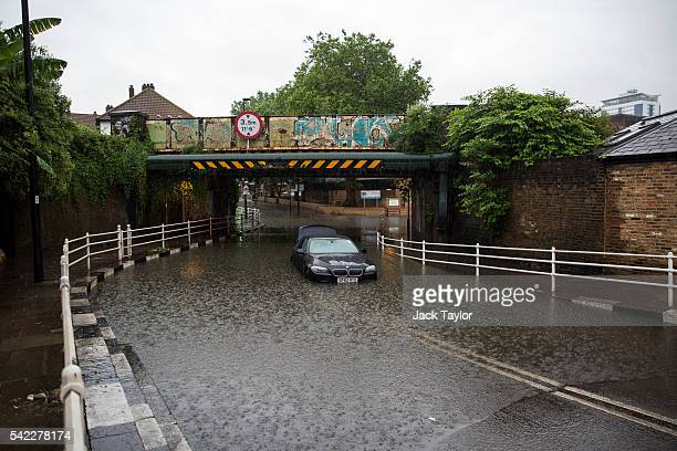 A car is abandoned under a bridge in Battersea after getting stuck in floodwater water on June 23 2016 in London England Overnight thunderstorms have...