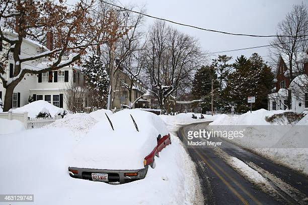 A car is buried in a snow bank on February 10 2015 in Cambridge Massachusetts Boston was hit with its third major snow storm in three weeks closing...