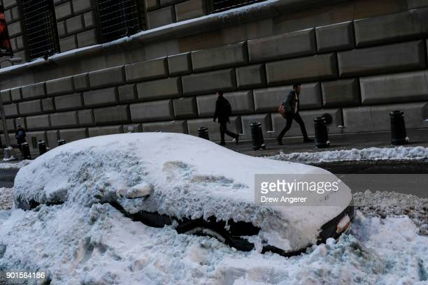 A car is buried in the plowed snow in the Financial District January 5 2018 in New York City Brutally cold temperatures and wind chills are expected...