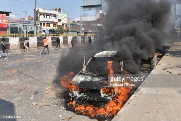 Car is burnt during violent clashes between anti and pro CAA demonstrations at Bhajanpura on February 24, 2020 in New Delhi, India. A Delhi Police...