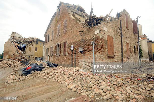 A car is crushed under fallen masonry beside a devastated house following an earthquake on May 20 2012 in Ferrara Italy At least four people were...