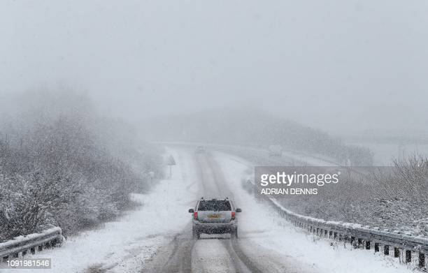 TOPSHOT A car is driven along a slip road leading to the snow and sleetcovered A34 road a near Chievely in Berkshire west of London on February 1...