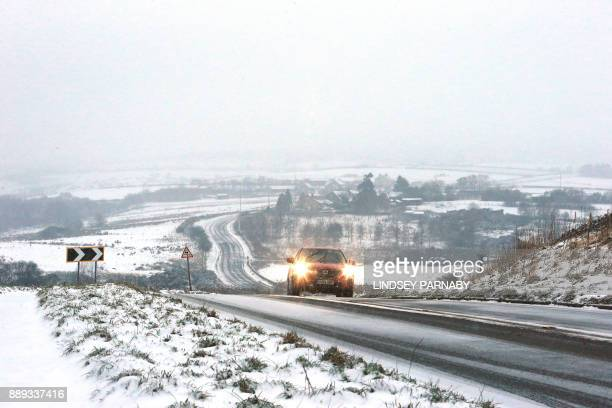 A car is driven along a snowcovered road near Hathersage in Derbyshire northern England on December 10 2017 Heavy snow fell across northern and...