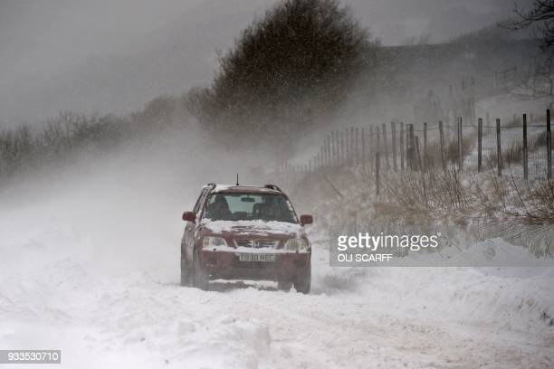 A car is driven along the A670 in snow near the village of Diggle east of Manchester in northern England on March 18 as the wintry weather makes a...