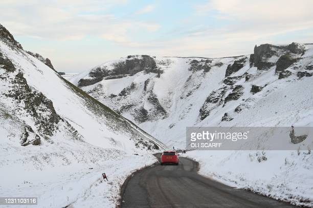 Car is driven down Winnats Pass through snow-covered countryside near Castleton in The Peak District in northern England on February 11 as the UK's...