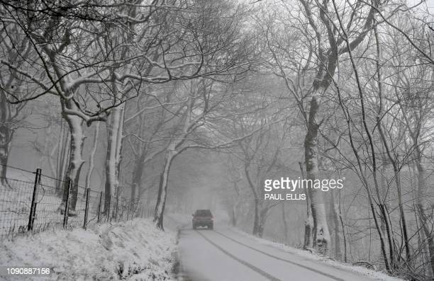 A car is driven on a snowcovered road on Mam Tor near Castleton central England on January 29 2019