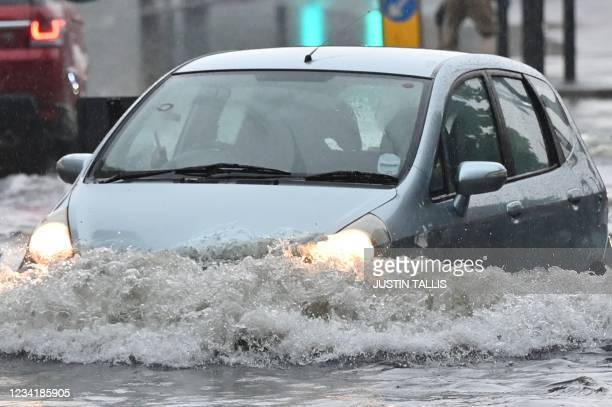Car is driven through deep water on a flooded road in The Nine Elms district of London on July 25, 2021 during heavy rain. - Buses and cars were left...