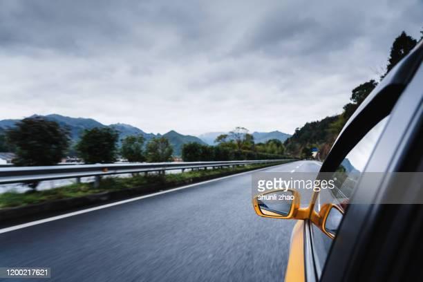 a car is driving on the mountain side road - rijden een motorvoertuig besturen stockfoto's en -beelden