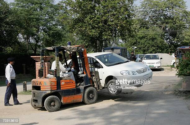 A car is moved out of the way to make space for the Royal convoy at Fatima Jinnah Womens University on the third day of the Royal Tour of Pakistan on...