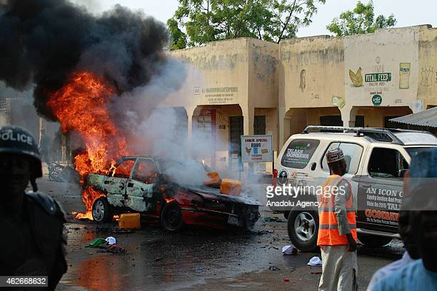 A car is on fire after a suicide bombing which was staged by a suspected female suicide bomber near a campaign rally at Pantami Stadium attended by...