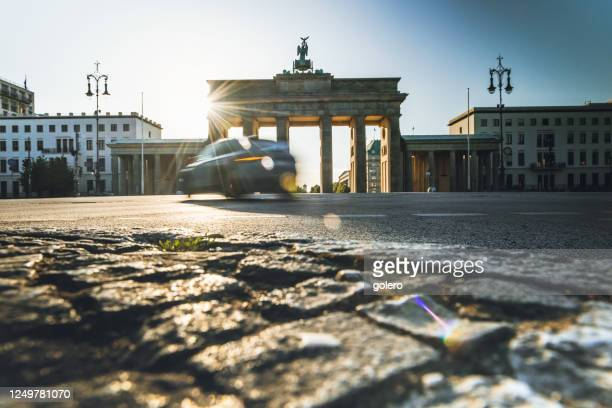car is passing brandenburger tor at sunrise hour - central berlin stock pictures, royalty-free photos & images