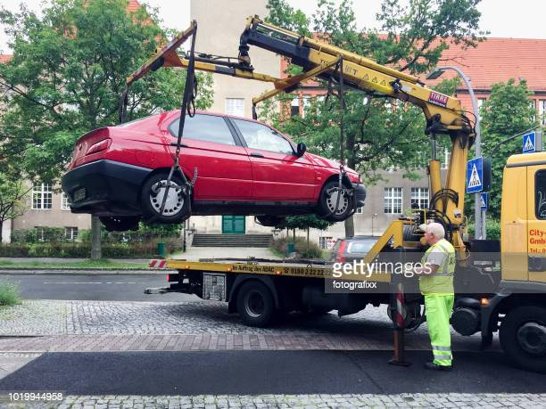 a car is picked up by employee of towing service - tow truck stock photos and pictures