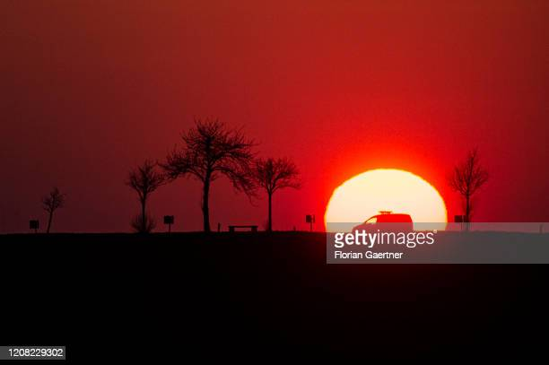 Car is pictured as silhouette during sunset on March 25, 2020 in Gebelzig, Germany.