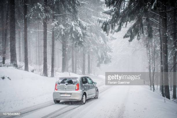 A car is pictured on a narrow road during snow fall at the Jizera Mountains on January 03 2019 in Bedrichov Czech Republic