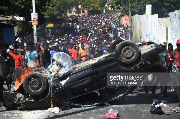 TOPSHOT A car is placed as a barricade by demonstratos during clashes in the center of Haitian capital PortauPrince on February 12 as a sixth day of...