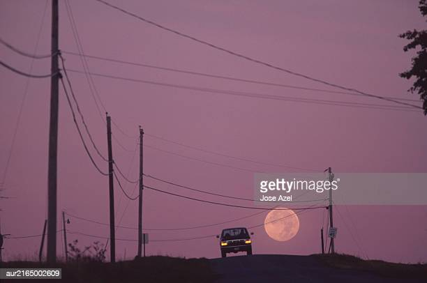 a car is seen as the moon sets at dawn and the sky begins to lighten, maine, usa. - luna llena fotografías e imágenes de stock