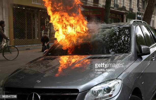 A car is seen burning as masked protesters clash with French CRS riot forces during the May Day in Paris France on May 01 2018