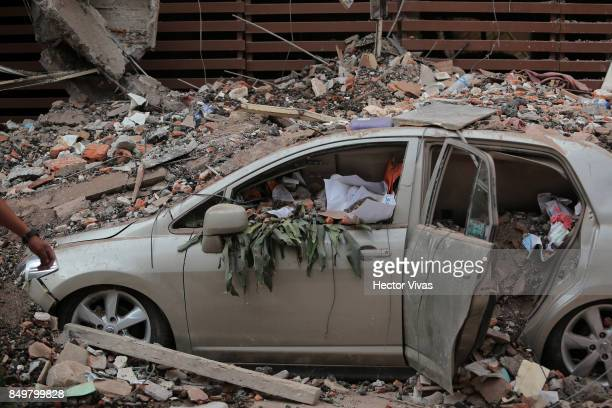 A car is seen destroyed because of the rubble from a building knocked down by a magnitude 71 earthquake that jolted central Mexico damaging buildings...