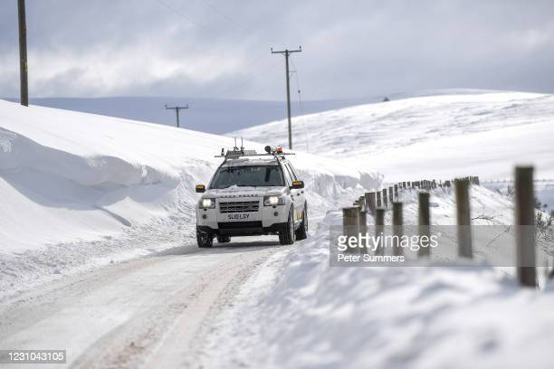 Car is seen driving past high snow drifts on February 8, 2021 in Cabrach, United Kingdom. Heavy snow in Scotland and South East England over the...