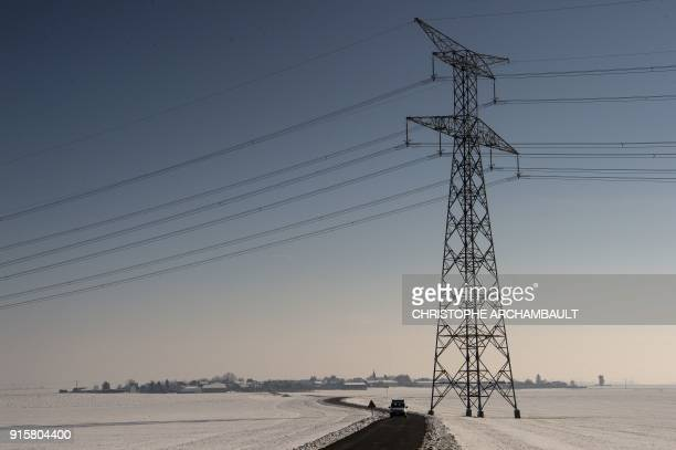 A car is seen on a road lined with snowcovered fields outside Artenay near Orleans some 120 km south of Paris on February 8 2018 / AFP PHOTO /...