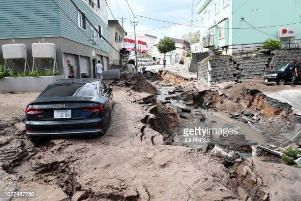 TOPSHOT A car is seen stuck on a road damaged by an earthquake in Sapporo Hokkaido prefecture on September 6 2018 A powerful 66magnitude quake rocked...