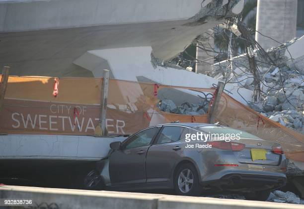 A car is seen stuck under the rubble as law enforcement and members of the National Transportation Safety Board investigate the scene where a...