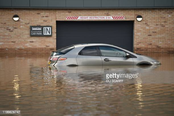 A car is seen submerged as flood water covers the roads and car parks in Mytholmroyd northern England on February 9 after the River Calder burst its...