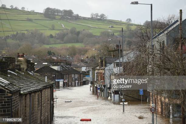 A car is seen submerged as flood water covers the roads in Mytholmroyd northern England on February 9 after the River Calder burst its banks as Storm...