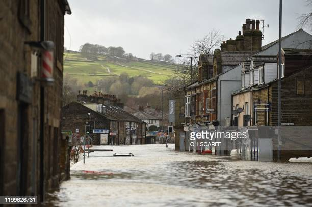 TOPSHOT A car is seen submerged as flood water covers the roads in Mytholmroyd northern England on February 9 after the River Calder burst its banks...