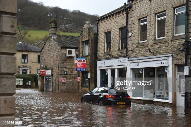 A car is seen submerged in floodwater in the streets of Hebden Bridge northern England on February 9 as Storm Ciara swept over the country Britain...