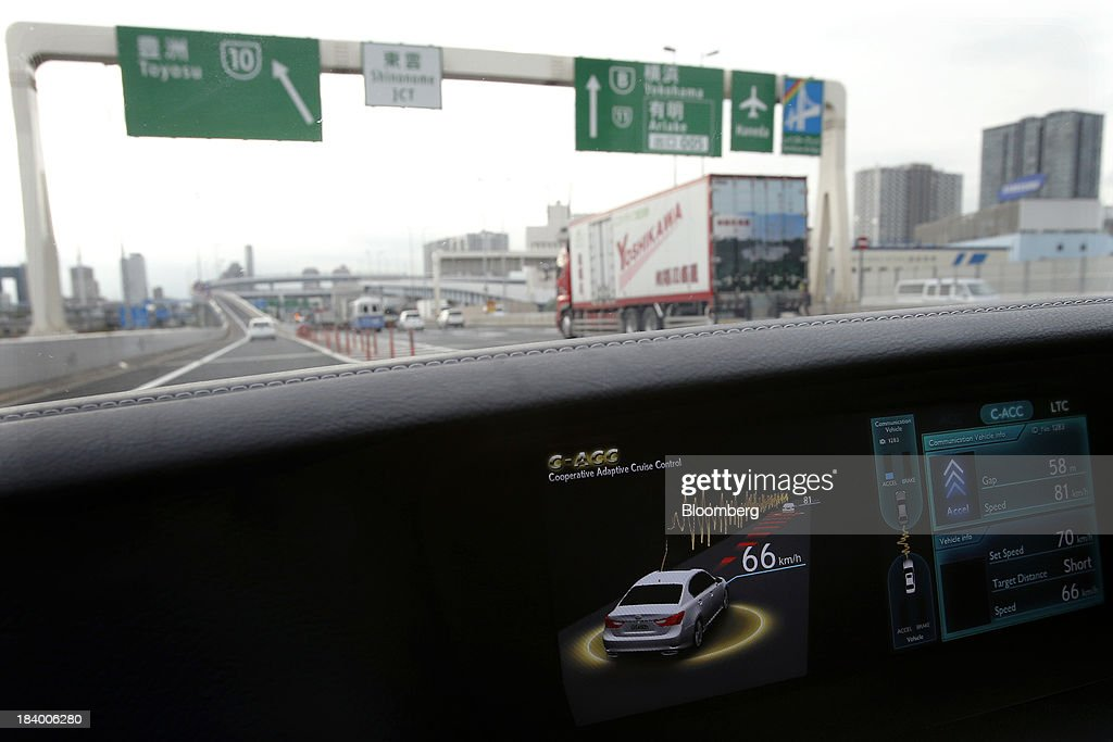 A car is seen through the windscreen as a monitor displays the status of the Cooperative Adaptive Cruise Control (CACC) technology in a Toyota Motor Corp. Lexus vehicle, equipped with the Automated Highway Driving Assist (AHDA) support system, during a media briefing on the company's advanced technologies in Tokyo, Japan, on Thursday, Oct. 10, 2013. Toyota, the world's largest automaker, will introduce systems in about two years enabling cars to communicate with each other to avoid collision. Photographer: Kiyoshi Ota/Bloomberg