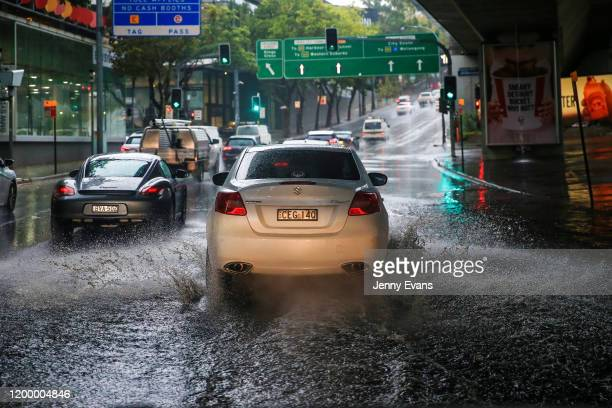 A car is seen traveling through flooded streets in Rushcutters Bay as rain falls on January 17 2020 in Sydney Australia A severe thunderstorm warning...