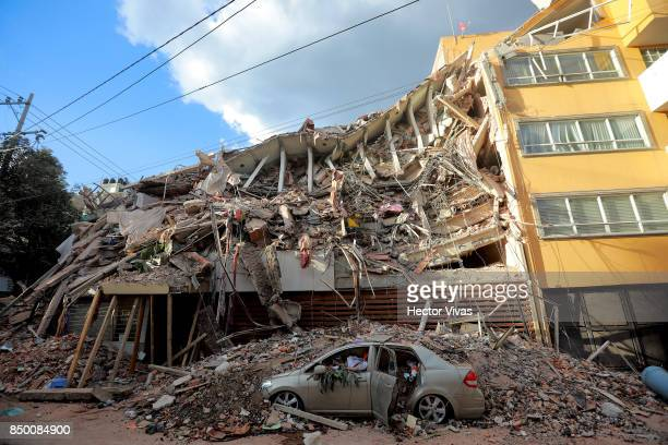 A car is seen under the debris of a collapsed building after the magnitude 71 earthquake jolted central Mexico damaging buildings knocking out power...