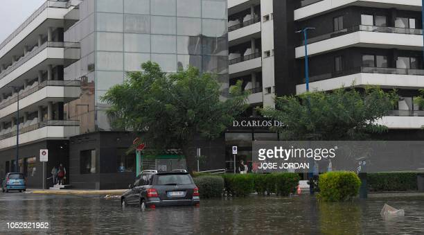 A car is stranded in the water on a flooded street in Peniscola on October 19 during heavy rains that hit eastern Spain
